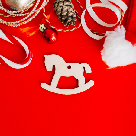 Wooden decoration on the Christmas tree in the form of rocking horses on a red background surrounded by Christmas elements. Place for text.