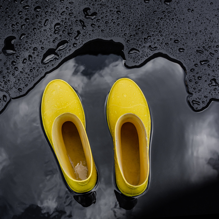 Yellow rubber boots stand in a puddle in which the clouds are reflected. Black background, top view.