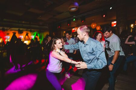 MOSCOW, RUSSIAN FEDERATION - OCTOBER 13, 2018: A middle-aged couple, a man and a woman, dance salsa among a crowd of dancing people in a nightclub Tiki bar. Long exposure, blurred motion. Editorial