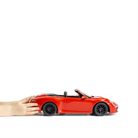 Baby hands holding red toy car isolated on white background. Copy space Editorial