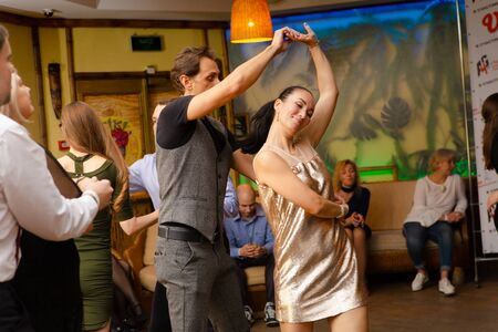 Moscow, Russia-January 19, 2019: A middle-aged couple, a man and a woman, dance salsa among a crowd of dancing people in a nightclub Tiki bar.