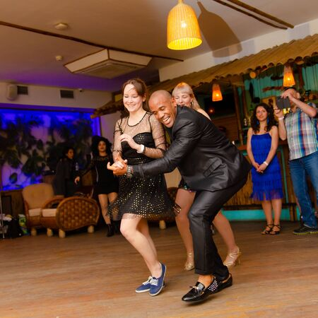 Moscow, Russia-January 19, 2019: Cuban man dancing salsa with two girls at the club. Editorial