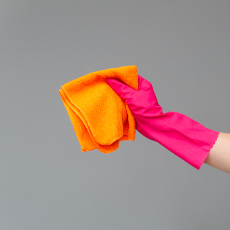 A hand in a rubber glove holds a bright microfiber duster on a neutral background. Сoncept of bright spring, spring cleaning. Stock Photo