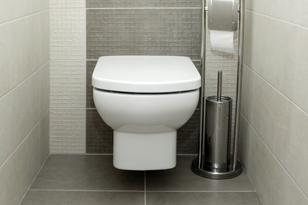 Toilette bianca in bagno moderno con portarotolo e scopino.