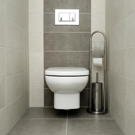 Biała muszla klozetowa w nowoczesnej łazience z uchwytem na papier i szczotką toaletową. Zdjęcie Seryjne