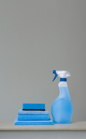 Cleaning blue spray bottle with plastic dispenser, sponge and cloth for dust  on grey background. Cleaning tools. Copy space. Archivio Fotografico