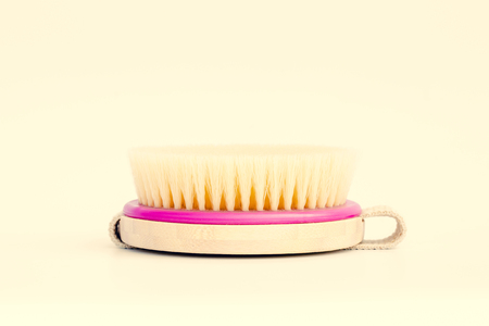Dry body massage brush on white background at sunny day. Tool for smooth, glowing and soft skin. Copy space. Toned. Foto de archivo