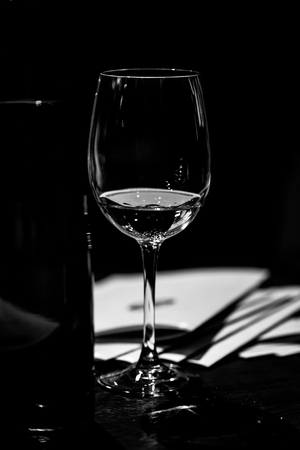 Wine tasting. On the wooden table is a beautifully illuminated glass of wine. Next to the bucket for cooling wines and brochures presented at the exhibition samples. BW.
