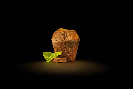 Chocolate fondant with chocolate pieces and mint leaves, sprinkled with cocoa. Isolated on black background. Frontal view.