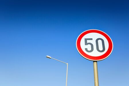 Traffic sign speed limit on the background of blue cloudless sky and street lamp. 写真素材 - 129839880