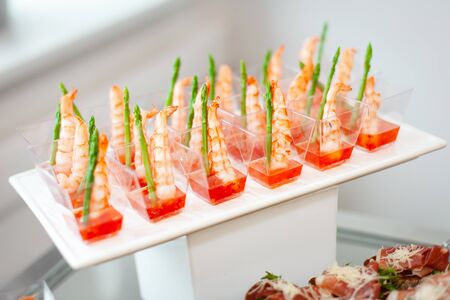 Food at the event: disposable plastic cups with snacks - shrimp with asparagus and sweet and sour sauce. Products included in the ketodiet. Stock fotó - 129839882