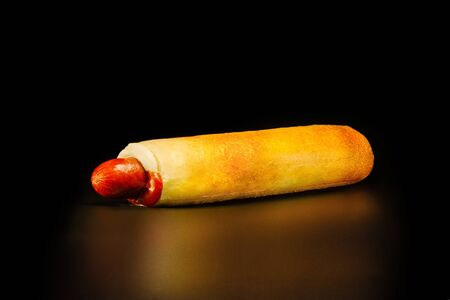 Czech hot dog is the most common on-the-go meal  - sausage in a wheat bun with sauce . Black background. Stock fotó