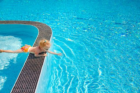 The little cute blonde toddler girl , lying on the side of the pool, touching the water.