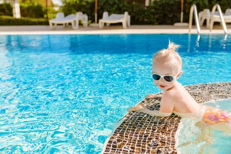 Cute little baby with sunglasses swimming in the pool, holding onto the side and looking at the water