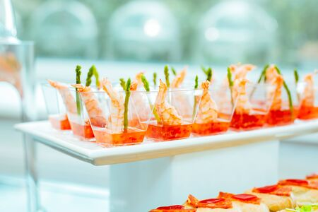 Food at the event: disposable plastic cups with snacks - shrimp with asparagus and sweet and sour sauce. Products included in the ketodiet. Stock fotó