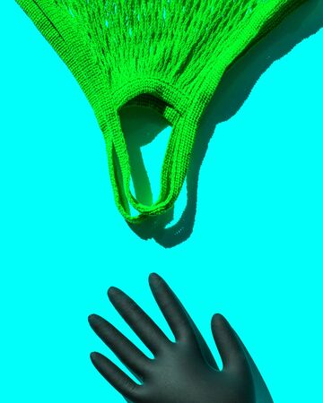 A reusable shopping bag and a hand in a black disposable glove. Pop art style. Top view. Place for text Imagens