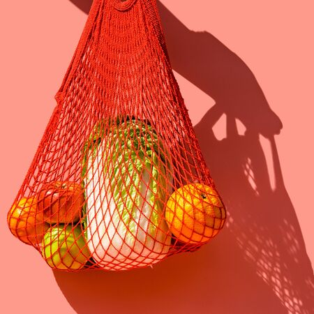 Red string bag with vegetables and fruit on a pink background. The concept of zero waste, healthy lifestyle and conscious consumption.
