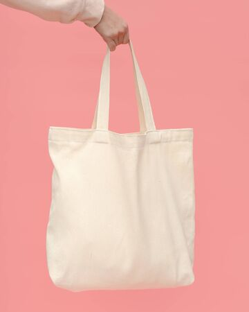 A woman's hand holds a light cotton reusable shopping bag on a pink background. The concept of zero waste. Imagens