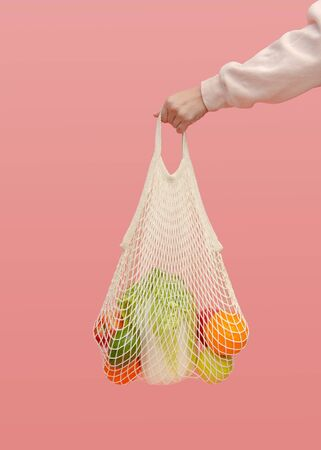 A woman's hand holds a mesh bag with vegetables and fruit on a pink background. The concept of zero waste and healthy food. Reusable shopping bag for going to the supermarket instead of plastic bags.