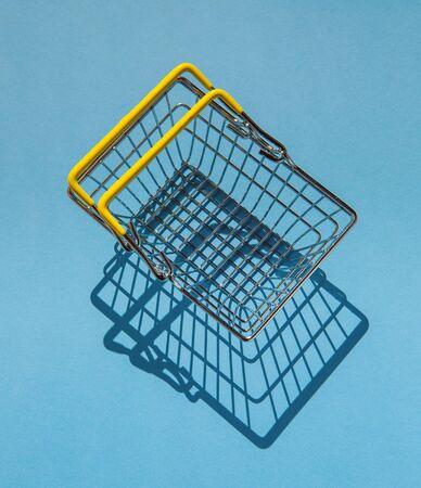 Metal shopping basket. The symbol of retail trade. Top view.  Minimalism.