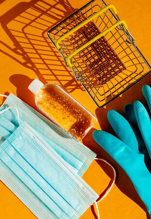 Personal protection kit for shopping during the coronavirus pandemic: individual face masks, gel sanitizer, hand gloves and shopping basket. Orange background, contrasting shadows. The view from the top. Imagens