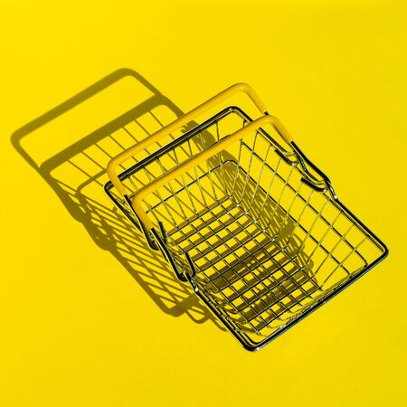 Metal mesh shopping basket in a supermarket. The view from the top. Yellow background.