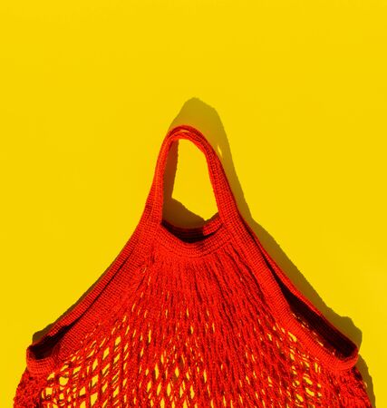 Reusable bright red shopping bag-a string bag. Zero waste concept. Yellow background, pop art style. Top view.