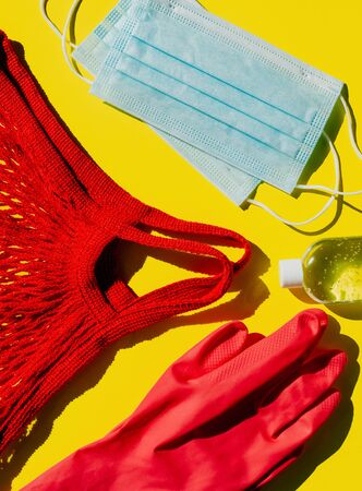 Covid personal protection kit - 19 visits to shops and other public places during the pandemic. Antiseptic, face masks, gloves and string bag on a yellow background.