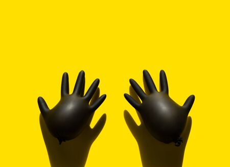 Two inflated medical black latex gloves on a yellow background. Pop art style. Imagens