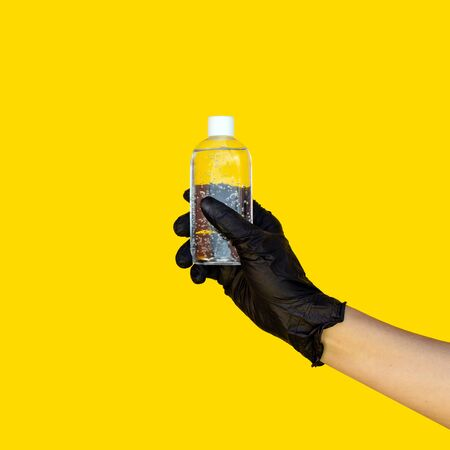 A hand in a protective surgical glove holds a bottle of gel sanitizer. A call to take care of hygiene during the coronavirus pandemic. Space for text. Yellow background
