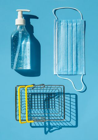 Personal protection kit for shopping during the coronavirus pandemic: face mask, gel sanitizer and shopping basket. Blue background, contrasting shadows. The view from the top. Imagens