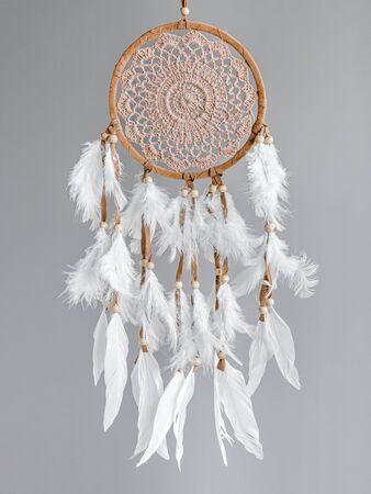 Atrapasueños marrón con plumaje blanco sobre fondo gris. Decoración de interiores. Atrapasueños nativo americano