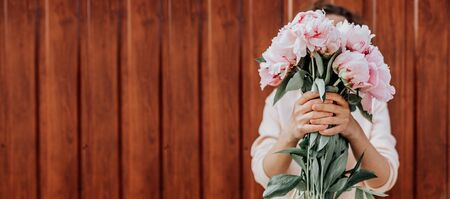 A faceless girl holds a bouquet of peonies. Soft focus. Flower delivery incognito. Faceless. Banner, copy space.