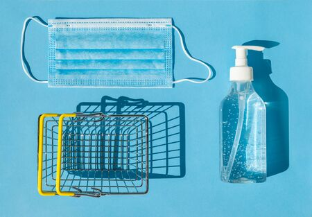 The concept of security of the buyer during the epidemic of kovid-19. Hand sanitizer, individual face mask and metal shopping basket in the store. Blue background, top view.