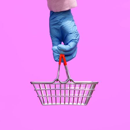 A woman's hand in a disposable bright glove holds a shopping metal basket from a supermarket on a lilac background. The safety of customers during the epidemic of coronavirus. Pop art style.