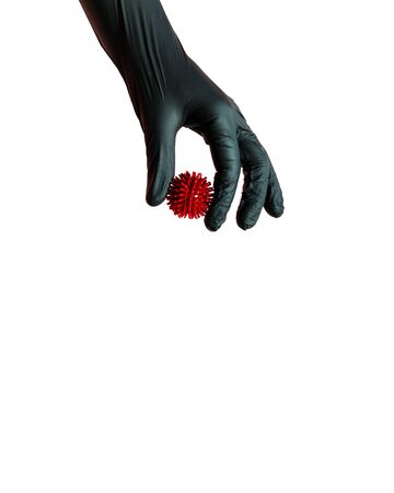 A hand in a protective black glove holds a model of the covid-19 virus . Isolated on a white background. The concept of protection against coronovirus, compliance with hygiene rules and preventive measures.