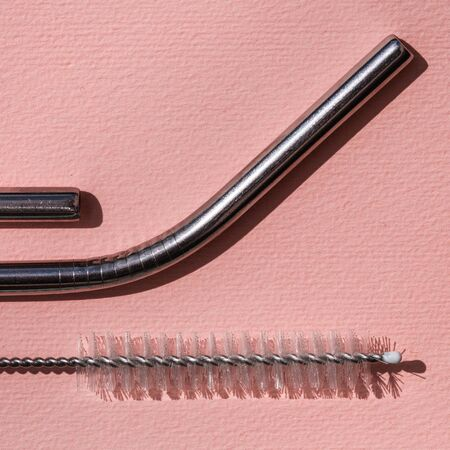 Ecological reusable tubules for drinking. Zero waste concept. Metal tube for drinking and brush for cleaning on fuchsia background. Close up. Imagens