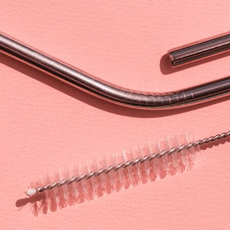 Reusable stainless steel straws and cleaning brush  on pink background, eco friendly lifestyle. Concept zero waste. Macro. pop art style.