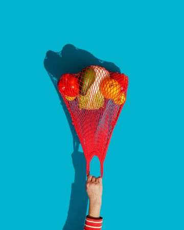 A woman's hand holds a bright red string bag -a reusable compact shopping bag filled with fresh vegetables and fruit. Flies away like a balloon. The concept of zero waste. The style of pop art. Imagens