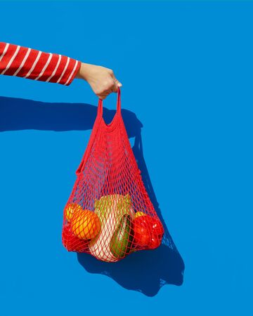 Hand with a red string bag filled with fresh vegetables and fruits from the market. The concept of zero waste and healthy eating. The style of pop a