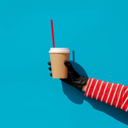 A hand in a disposable glove holds a disposable Cup with a drink and a disposable plastic straw. Zero waste against coronavirus. Return of single-use plastic during the pandemic. Imagens