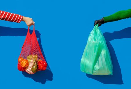 A hand with a string bag filled with fresh vegetables and fruit and a hand in a disposable glove holding a plastic bag. Zero waste against covid. Return of disposable plastic during epidemic. Imagens