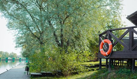 A red and orange lifebuoy hangs on the terrace near the fishing pier in a country hotel.