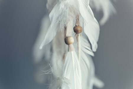 Plumage and beads of a Native American Dreamcatcher. Close up. Selective focus. Imagens - 148011293