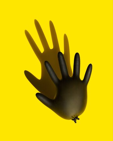 Disposable black latex glove to protect your hands from coronavirus, inflated like a balloon. The concept of protecting hands from coronovirus infection.  The style of pop art. The view from the top. Copy space.