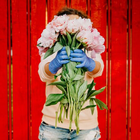 A girl in front of a red fence in protective gloves holds out a bunch of peonies. The face is hidden behind a bouquet of flowers. Concept of safe delivery to the Prairie of the risk of coronavirus infection.