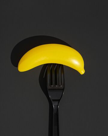 A black disposable plastic fork with a plastic banana impaled on it. The concept of ecological payback for excessive use of plastic by humans. Black background. Top view.
