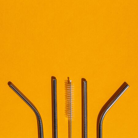 Kit of reusable metal straws on orange background. Environmental reusable products, zero waste. Copy space, top view. Imagens