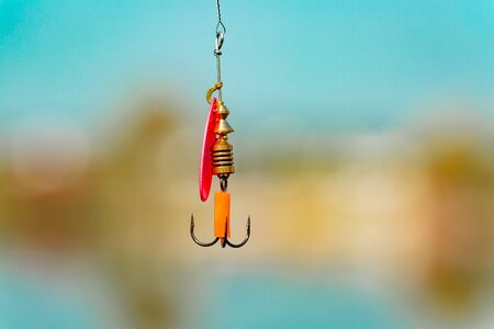 A bright spinner with a triple hook for fishing hangs on a fishing line above the water. Selective focus. Close up.