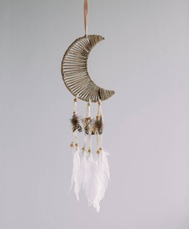 Dreamcatcher in the shape of a Crescent moon on a gray background. Interior decoration. Native American Dreamcatcher. Imagens